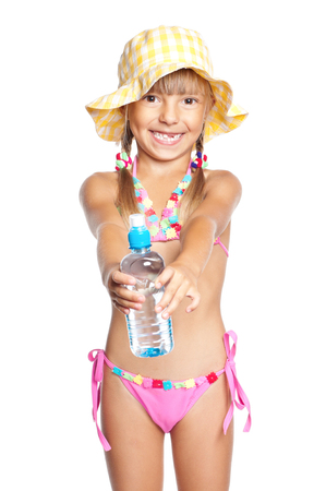child laughing: Happy little girl in swimsuit with bottle of water. Laughing child in hat, isolated on white background. Stock Photo
