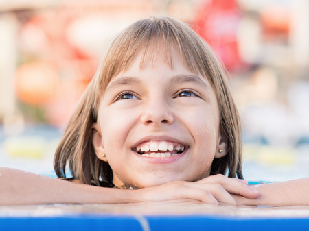 Close-up portrait of happy girl in the swimming pool at aquapark. Cute child having fun enjoyable time on vacation.