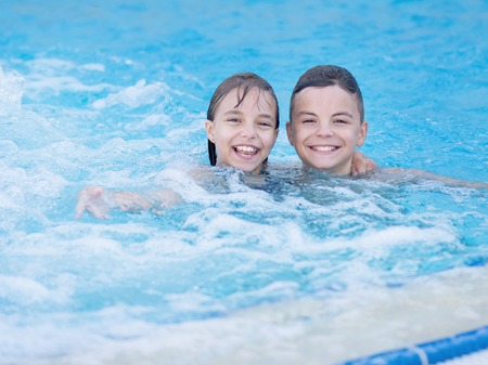 enjoyable: Smiling beautiful children in the swimming pool at aquapark. Happy teen boy and girl - brother and sister having fun together enjoyable time on vacation. Stock Photo