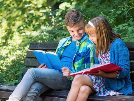 school yard: Children reading book at park. Outdoor portrait of teen boy and girl. Siblings doing homework in summer garden. Cute kids study in school yard.