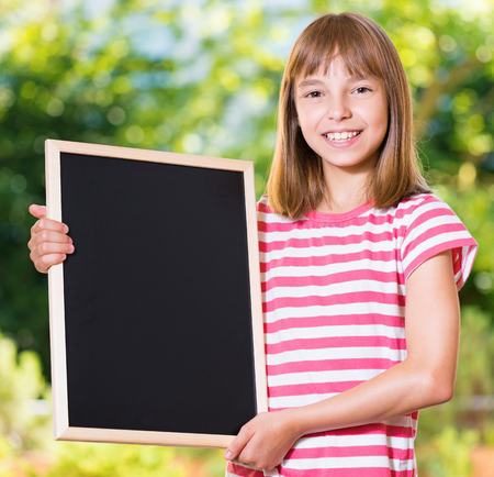 Outdoor portrait of happy girl 10-11 year old with small blackboard. Back to school concept. Young student beginning of class after vacation.