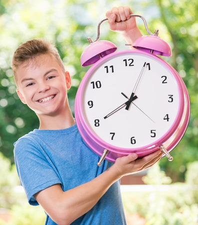 Outdoor portrait of happy teen boy 12-14 year old with big alarm clock. Back to school concept. Beautiful schoolboy posing outdoors. Young student beginning of class after vacation.