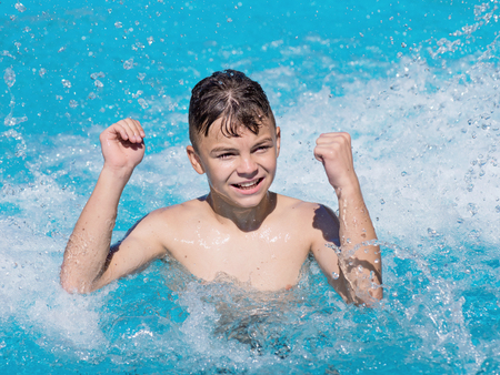 enjoyable: Happy teen boy jumping in the swimming pool at aquapark. Cute child having fun enjoyable time on vacation. He laughing and splashing water.