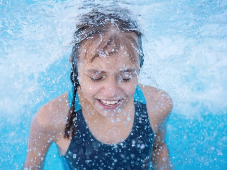enjoyable: Close-up portrait of happy girl in the swimming pool at aquapark. Cute child having fun enjoyable time on vacation.