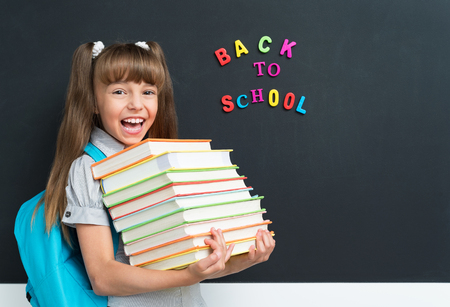Back to school concept. Cute pupil with books at the black chalkboard in classroom. Stock Photo