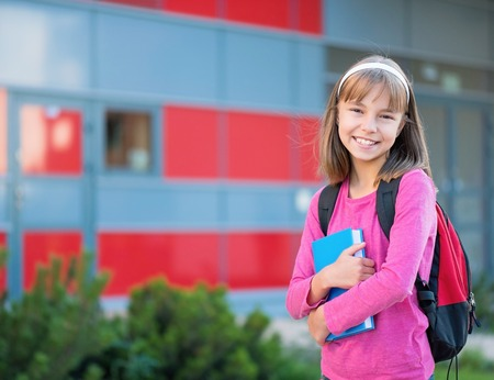 Outdoor portrait of happy girl 10-11 year old with book and backpack. Back to school concept. Stock Photo