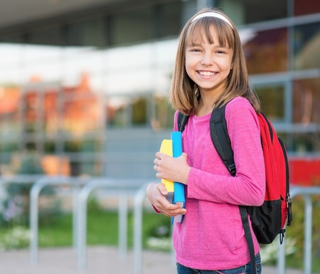 white back: Happy girl holding books in school yard. Outdoor portrait.
