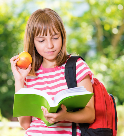 Outdoor portrait of happy girl 10-11 year old with book and apple. Back to school concept.
