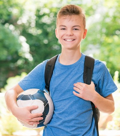 white back: Outdoor portrait of happy teen boy 12-14 year old with soccer ball and backpack. Back to school concept.