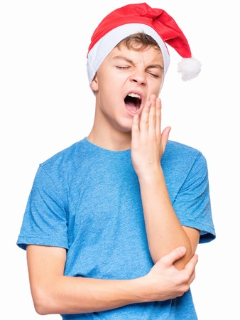Half-length portrait of caucasian teen boy wearing Santa Claus hat. Teenager in blue t-shirt is yawning with closed eyes. Holiday Christmas concept - tired cute child isolated on white background. Stock Photo