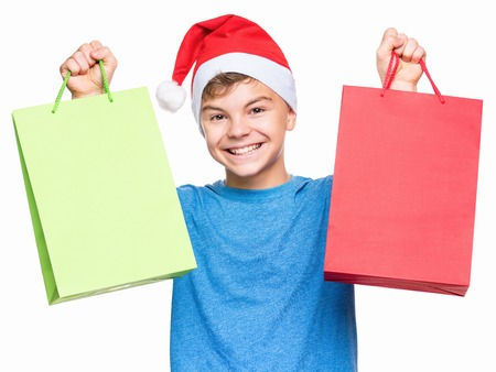 tenager: Half-length portrait of smiling teen boy wearing Santa Claus hat, surprised. Caucasian tenager in blue t-shirt, holding shopping bags. Holiday Christmas concept - happy cute child isolated on white background.