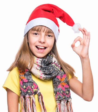 Half-length portrait of caucasian girl wearing Santa Claus hat. Schoolgirl looking at camera and making ok gesture. Holiday Christmas concept - happy cute child isolated on white background.