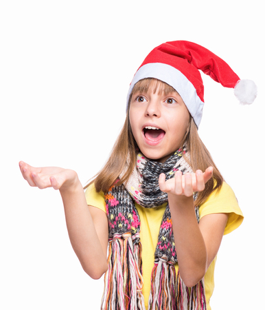 Caucasian girl wearing Santa Claus hat. Funny kid  trying to catch something, isolated on white background. Holiday Christmas concept - happy cute child reaching out her palms and catching somethin.