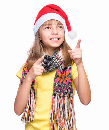 Half-length portrait of caucasian girl wearing Santa Claus hat. Funny kid in yellow t-shirt pointing upwards. Holiday Christmas concept - happy cute child isolated on white background.