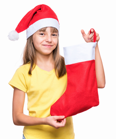 Portrait of caucasian girl wearing Santa Claus hat. Happy schoolgirl in yellow t-shirt, isolated on white background. Holiday concept - funny cute child holding Christmas sock.