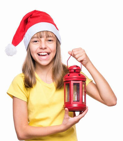 Studio portrait of a beautiful caucasian girl wearing Santa Claus hat, isolated on white background. Holiday Christmas concept - funny child holding red lantern, she is laughing and looking very happy.