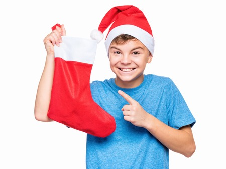 Portrait of caucasian teen boy wearing Santa Claus hat. Happy teenager in blue t-shirt, isolated on white background. Holiday concept - funny cute child holding Christmas sock. Stock Photo