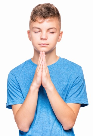 alabando a dios: Portrait of caucasian teen boy closed his eyes and saying prayers. Handsome child praying and praising God, isolated on white background. Religious image - teenager hands clasped in prayer prays to God. Foto de archivo