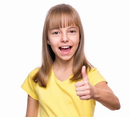 Half-length emotional portrait of caucasian little girl wearing yellow t-shirt. Funny kid making thumb up gesture, isolated on white background. Beautiful child laughing looking very happy.