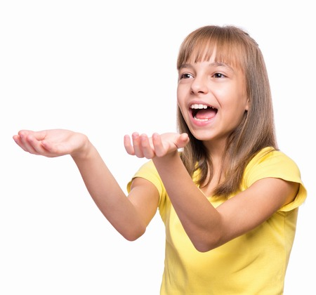 catches: Happy cute child reaching out her palms and catching something. Half-length emotional portrait of caucasian little girl wearing yellow t-shirt, surprised. Funny kid trying to catch something, isolated on white background.