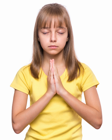 alabando a dios: Portrait of caucasian girl closed her eyes and saying prayers. Beautiful child praying and praising God, isolated on white background. Religious image - kid hands clasped in prayer prays to God.