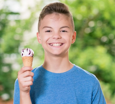 Outdoor portrait of happy teen boy 12-14 year old with ice cream in waffles cone. Cute child holding ice-cream and making gladness face while walking in the park. Lucky teenager eating and licking ice cream. Stock Photo