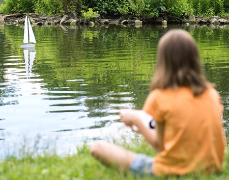 remote controlled: Girl playing with a remote controlled boat. Handmade model sailboat on lake - child with tablet. Out of focus girl. Selective focus limited to boat. Stock Photo