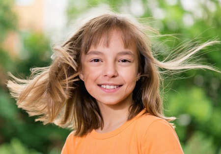 Portrait of a happy girl 10-11 year old, posing outdoors. Cute smiling child with flying hair looking at camera. Beautiful kid having fun in summer park. Stock Photo