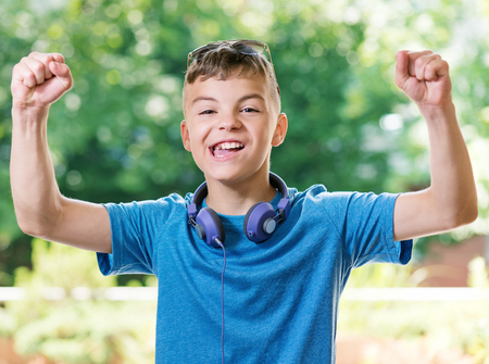 arms up: Victory screaming teen boy 12-14 year old. Funny winner boy with headphones and sunglasses posing outdoors. Portrait of a happy handsome teenager shouting with his hands up in summer park.