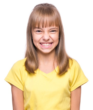 Little girl making funny face. Half-length emotional portrait of child wearing yellow t-shirt. Sad kid, isolated on white background. Beautiful smart serious ponder children.