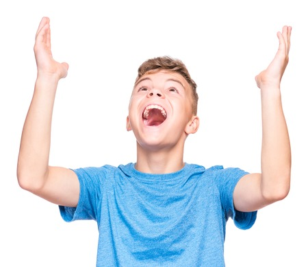 upgrowth: Happy cute child reaching out his palms and catching something. Half-length emotional portrait of caucasian teen boy wearing blue t-shirt, surprised. Funny teenager trying to catch something, isolated on white background.