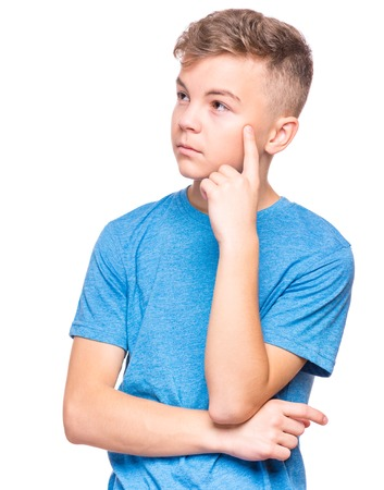Casual thinking guy - caucasian male model. Half-length emotional portrait of teen boy wearing blue t-shirt. Thoughtful teenager, isolated on white background. Handsome smart serious ponder child. Stock Photo