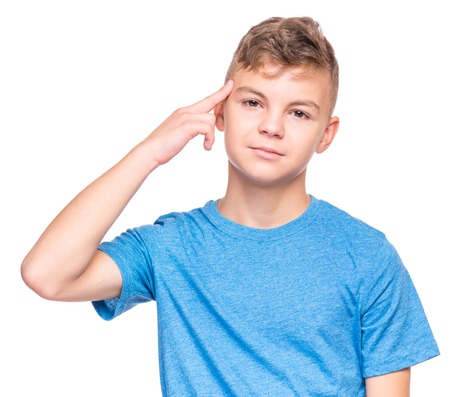 Teen boy making an imaginary gun shoot. Emotional portrait of bored teenager committing suicide with finger gun gesture. Child shooting hisself making finger pistol sign,  isolated on white background. Stock Photo