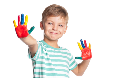 Eight year old boy with hands painted in colorful paints isolated on white background. Portrait of smiling kid ready for hand prints. Happy playful child looking at camera.