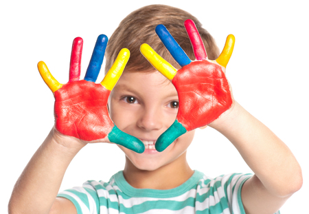 Eight year old boy with hands painted in colorful paints isolated on white background. Close up portrait of smiling kid ready for hand prints. Happy playful child looking at camera. Stock Photo