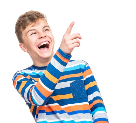 Emotional portrait of caucasian teen boy. Funny teenager pointing and looking upwards while laughing, isolated on white background. Handsome happy child pointing at copy space. Stock Photo