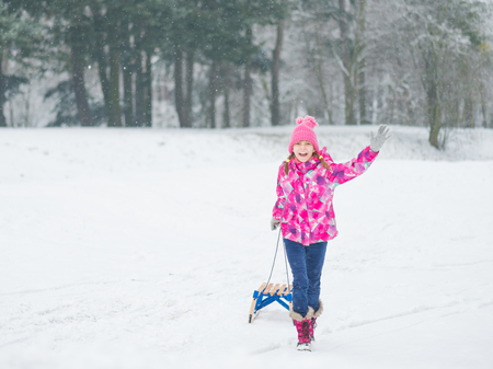 sledging people: Child play in snow with sled