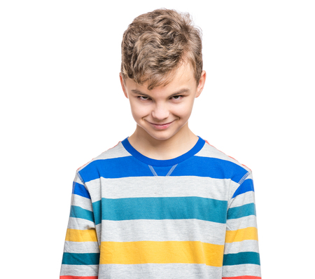 duplicitous: Teen boy making silly grimace - expressing cunning face. Upset child isolated on white background. Emotional portrait of caucasian teenager looking at camera.