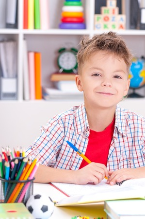 Happy smiling young boy sitting at desk in the classroom or home. Handsome child looking at camera. Stock Photo
