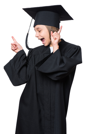 Emotional portrait of a graduate little happy girl student in a black graduation gown with hat, isolated on white background. Lucky cheerful schoolgirl celebrating triumph.