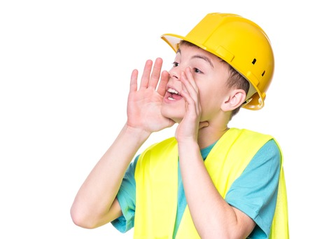 Emotional portrait of handsome caucasian teen boy wearing safety jacket and yellow hard hat. Happy child screaming and looking away, isolated on white background. Stock Photo