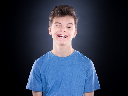 Cute playful teen boy winking at camera - close up emotional portrait. Head shot of handsome young child. Funny cut caucasian teenager on black background.
