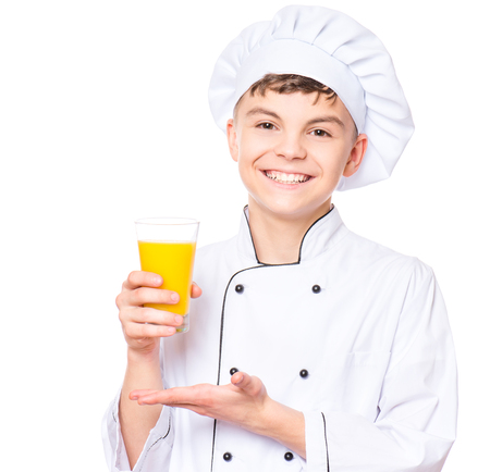 Handsome teen boy wearing chef uniform drinking fresh orange juice. Portrait of a happy cute male child cook with glass, isolated on white background. Food and cooking concept.