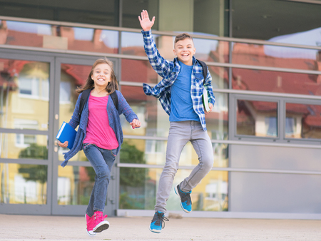 Happy children - boy and girl with books and backpacks on the first or last school day. Schoolchildren celebrating end of term. Students to complete academic year. Full length outdoor portrait. Stock Photo