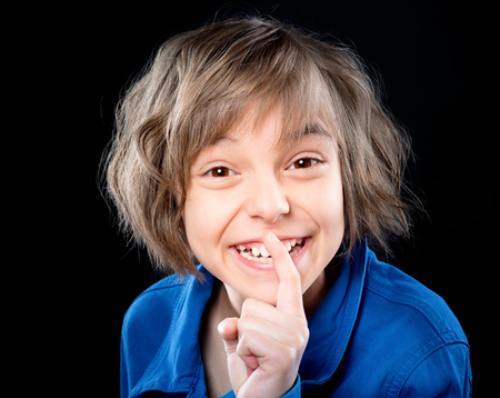 sh: Emotional portrait of attractive caucasian little girl with finger up to lips for making a quiet gesture, on black background. Child showing silence gesture looking at camera. Stock Photo