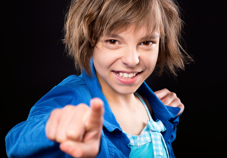 designate: Emotional portrait of attractive caucasian little girl pointing finger to you. Funny cute smiling child 10 year old looking at camera choosing you, on black background. Stock Photo