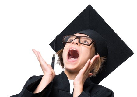 Portrait of a surprised graduate little girl student in a black graduation gown, hat and eyeglasses, looking up with wide open mouth - isolated on white background. Educational concept. Stock Photo