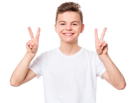 Witte t-shirt op tienerjongen. Knappe lachende kind maken overwinning gebaar, geïsoleerd op een witte achtergrond. Concept van je jeugd en mode of advertentie ontwerp. Mock up sjabloon voor ontwerp print. Stockfoto