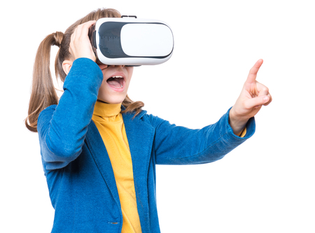 Happy amazed little girl wearing virtual reality goggles watching movies or playing video games, isolated on white background. Cheerful child looking in VR glasses and gesturing with his hands.