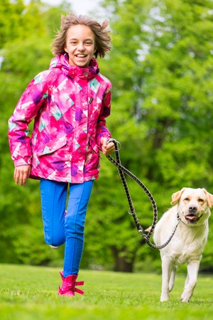 endear: Little girl with labrador retriever on walk in park. Child is running on green grass with dog - outdoor in nature. Pet, domestic animal and people concept.